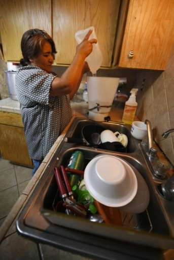 Maria Jimenez demonstrates how they use bottled water to wash dishes in the drought affected town of Monson, California on June