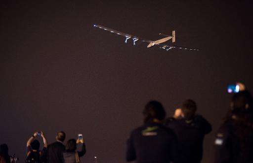 People take pictures as the Swiss-made solar-powered plane Solar Impluse 2 takes off from Nanjing's Lukou International Airport