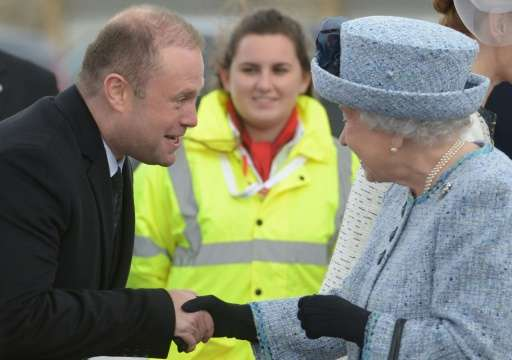 Queen Elizabeth II (R) is welcomed by Malta's Prime Minister Joseph Muscat on her arrival on the island on November 26, 2015