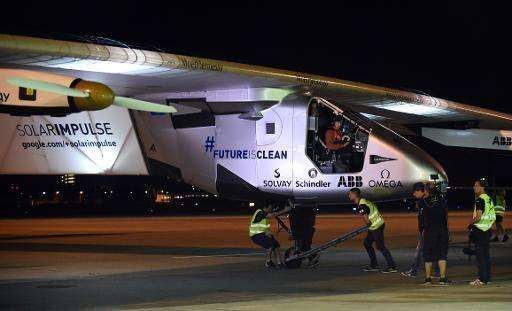 Swiss pilot Andre Borschberg (C, top) pictured aboard Solar Impulse 2 as ground crew push the plane prior to a scheduled take-of