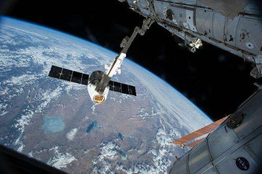 This NASA image taken April 17, 2015 shows the Canadarm 2 reaching out to grapple the SpaceX Dragon cargo spacecraft and prepare