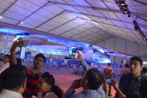 Visitors take photographs of the world's only solar powered aircraft 'Solar Impulse 2' in the hanger at Sardar Vallabhbhai Patel
