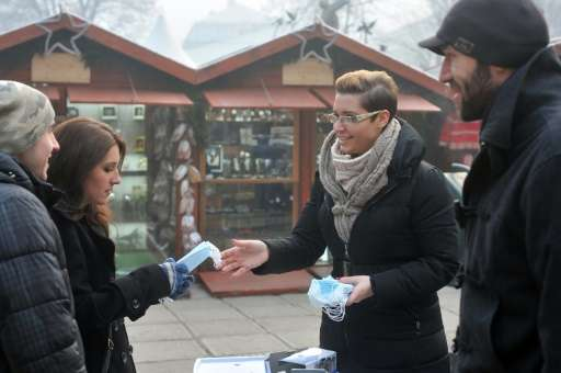 Volunteers pass out breathing masks in the centre of Sarajevo on December 23, 2015 amid choking smog that forced authorities to