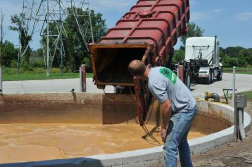 Farmer Ryan Rogers checks on a truck which has dumped food waste into a pit that feeds an anaerobic digester at Homestead Dairy