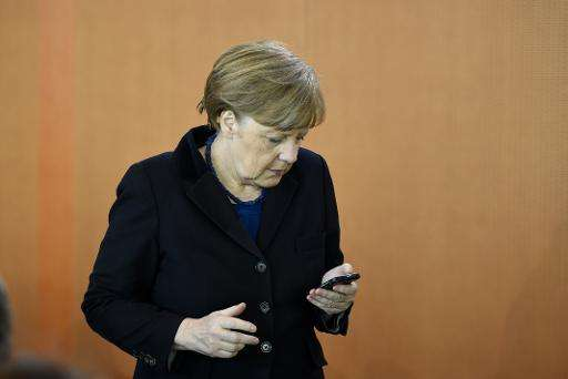 German Chancellor Angela Merkel checks her mobile phone as she arrives for the weekly cabinet meeting in Berlin on March 25, 201