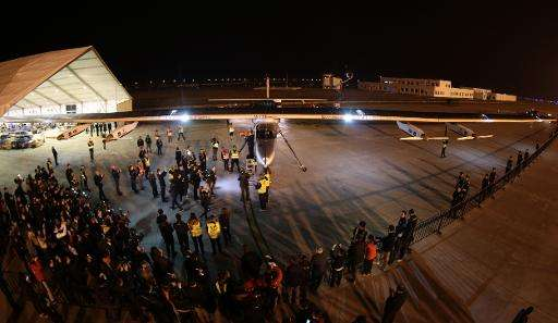Members of the media crowd around the solar powered aircraft Solar Impulse 2 in the early hours of April 22, 2015, after it land