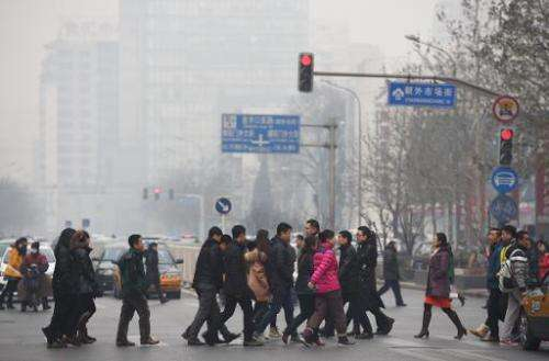 Pedestrians cross a road on a polluted day in Beijing on December 9, 2014