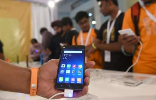 People look at Xiaomi's Mi4i smart phone and Mi Band during their launch in New Delhi on April 23, 2015