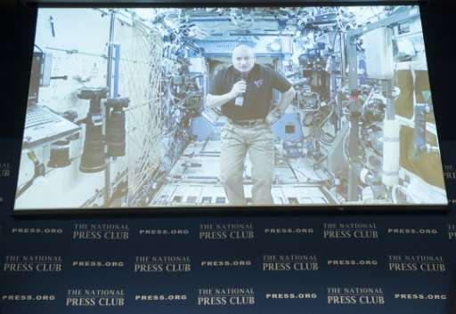 NASA Astronaut Scott Kelly, appearing live on video, speaks from the International Space Station during an event at the National