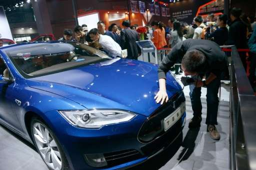 Visitors look at a Tesla car during the 16th Shanghai International Automobile Industry Exhibition in Shanghai on April 24, 2015