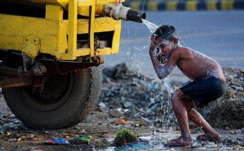 A boy washes himself from a roadside water tanker in Faridabad, a suburb of New Delhi, on March 18, 2015