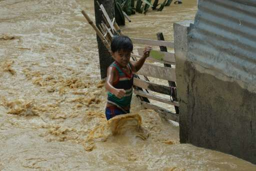 A child wades through floodwaters near his residence at a village in Santa Rosa town, Nueva Ecija province, north of Manila on O