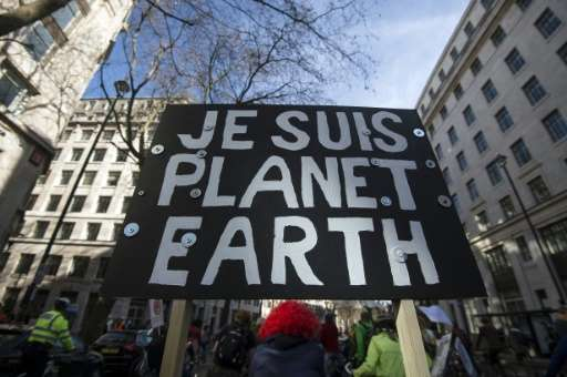 """A demonstrator carries a placard reading, """"Je suis Planet Earth"""" (""""I am Planet Earth"""") during The People's C"""
