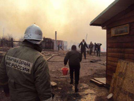 A firefighter and local residents extinguish a fire in a village in southeastern Siberia on April 12, 2015