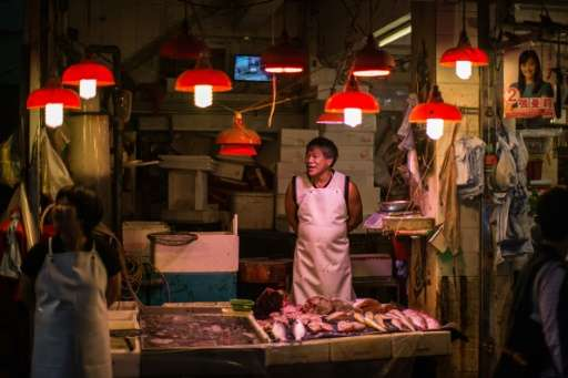 A fishmonger waits for customers in the Wanchai district of Hong Kong on November 3, 2015