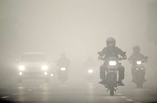 A heavy blanket of haze covers motorists travelling in Palangkaraya, capital of Central Kalimantan province on Indonesia's Borne