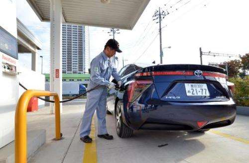 """A man refuels Toyota Motor's fuel cell vehicle """"Mirai"""" at a hydrogen station in Tokyo on November 17, 2014"""