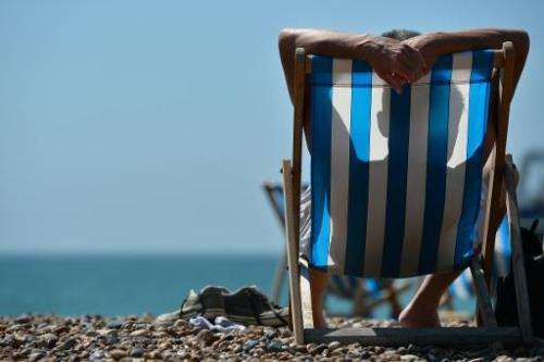A man relaxes on a deckchair on the beach in Brighton during hot weather on the southern English coast on August 1, 2013