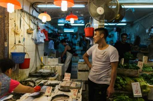 A man smokes as a customer (bottom L) selects fish from his stall in the Wanchai district of Hong Kong on November 3, 2015
