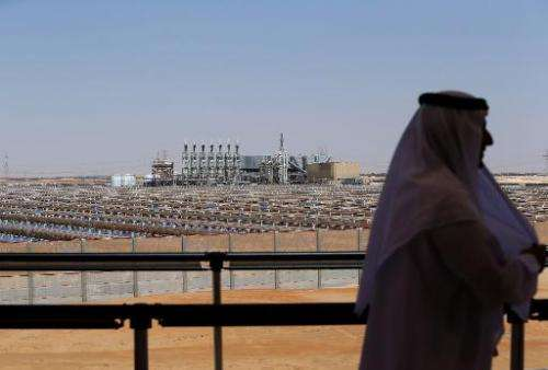 A man stands on a balcony overlooking the Shams 1 concentrated solar power (CSP) plant, in al-Gharibiyah district on the outskir