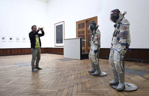 A man takes a picture of Soviet cosmonaut suits, on May 5, 2014, in Brussels, ahead of their auction on May 7. The London exhibi
