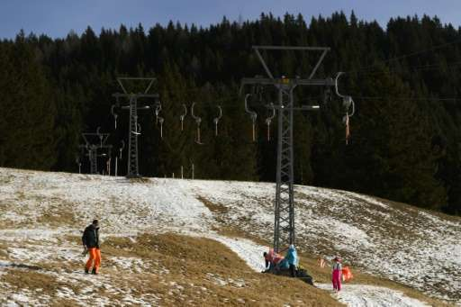 A man walks across a snowless ski slope in the Swiss Alps resort of Davos on December 12, 2015