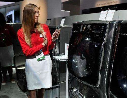 An LG representive uses a smartphone to control an LG front loading washing machine at the Consumer Electronics Show on January