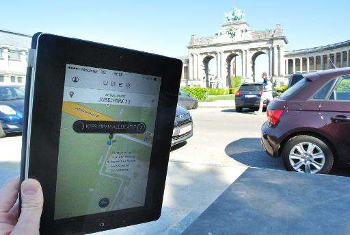 A person holds a tablet with the Uber application open in Brussels on April 16, 2014