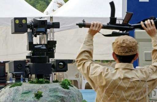 A sentry robot freezes a hypothetical intruder by pointing its machine gun during a 2006 test in Cheonan, South Korea