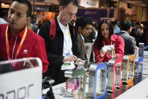 Attendees examine new smartphones at the Consumer Electronics Show in Las Vegas on January 6, 2015