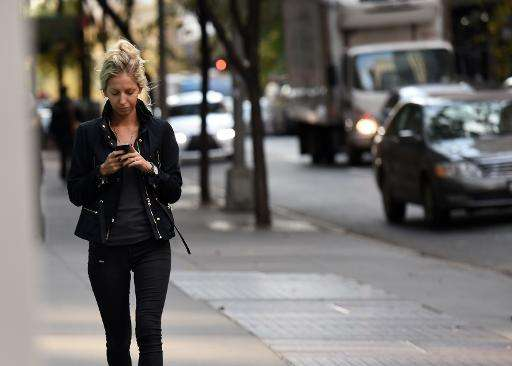 A woman uses her smart phone as she walks on November 13, 2014 in New York
