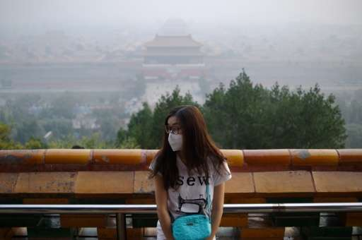 A woman wears a mask as she visits a park near the Forbidden City shrouded in haze in Beijing on October 7, 2015