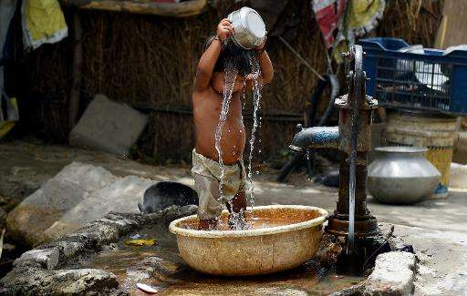 A young Indian child pours water on himself as he tries to cool himself off in New Delhi on May 28, 2015