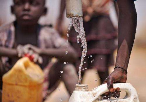 Children drink from a contaminated borehole at Rier village in South Sudan's Unity state near an abandoned oil treatment facilit