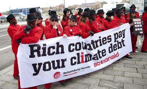 'Climate debt agents' from ActionAid demonstrate outside the venue of the ongoing COP15 UN Climate Change Conference in Copenhag