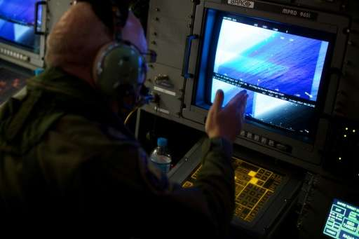 Crewman aboard an RAAF AP-3C Orion aircraft looks at his radar screens while searching for the missing Malaysia Airways Flight M