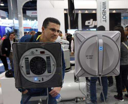 Dean Kurutz watches two WINBOT W930 window cleaning robots by Ecovacs Roboticsat the Consumer Electronics Show in Las Vegas on J