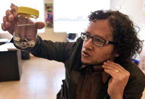 Ecuadorean scientist Juan Manuel Guayasamin displays a frog during an interview with AFP in Quito on March 31, 2015