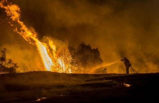 Firefighter Joe Darr douses flames of the Rocky fire along Highway 20 near Clearlake, California, on August 2, 2015