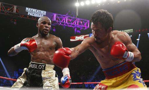 Floyd Mayweather (L) exchange punches with Manny Pacquiao during their welterweight unification championship bout on May 2, 2015