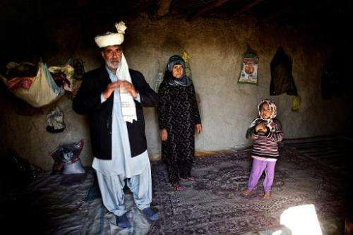 Iranian Annazar Sarani poses with his family inside their one-room mud house in the village of Sikhsar, where wooden boats sit o