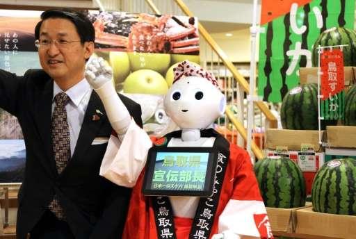 Japanese telecom giant Softbank's humanoid robot Pepper gestures alongside Tottori Prefecture Governor Shinji Hirai as they prom