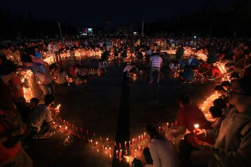 Local residents and volunteers attending a candle-light vigil for victims of the earthquake in Ludian county in Zhaotong, southw