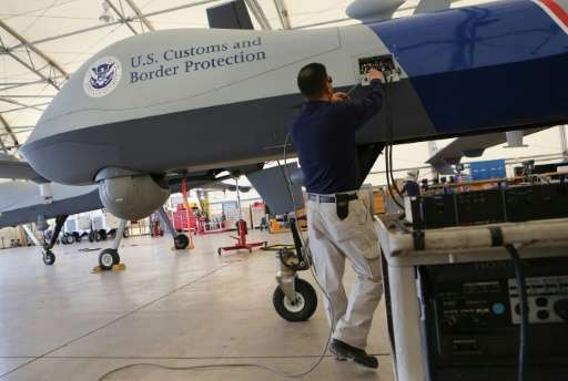 Maintenence personel prepare a Predator drone before its surveillance flight near the Mexican border on March 7, 2013 from Fort