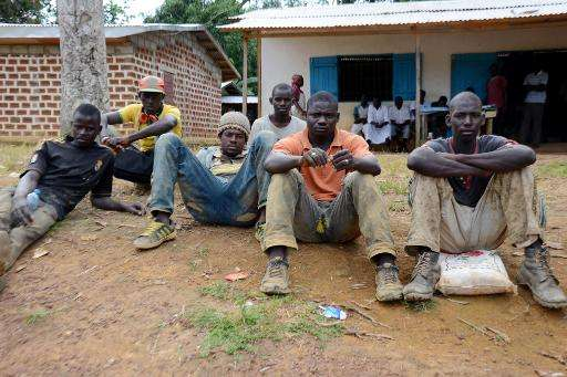 Malian migrant rubber plantation workers await for transport to collect them from the Olam factory in Batouri