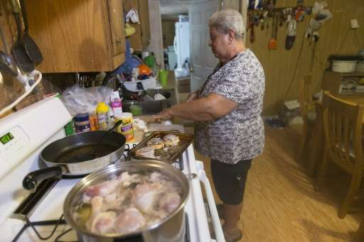 Marilyn Naquin cooks at her home on the Isle de Jean Charles, Louisiana but with no insurance, Naquin won't be able to rebuild t