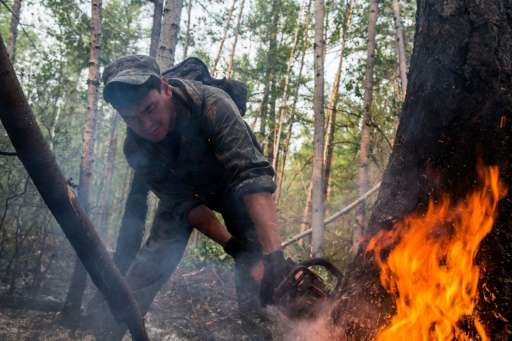 More than 5,000 Russian emergency workers are battling to put out wildfires raging across forestland in Siberia