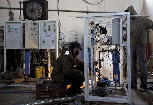 Palestinian labourers inspect a machine that makes seawater potable in Gaza city