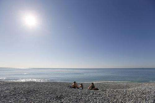 People enjoying warm temperatures on the beach in the French Riviera city of Nice on March 7, 2014