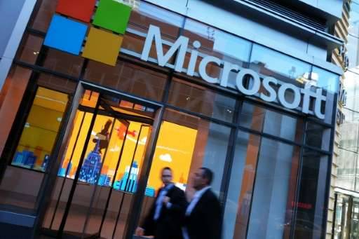 People pass by a Microsoft office in New York on October 6, 2015